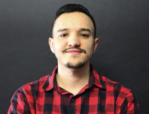 jovem homem pousando para foto. Ele veste um camisa xadrez vermelha com listras pretas