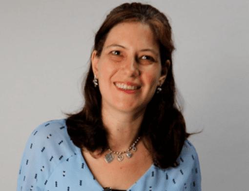 mulher vestindo uma blusa azul clara com detalhes em preto. Ela sorri para a foto, tem cabelos na altura dos ombros e usa com colar prateado