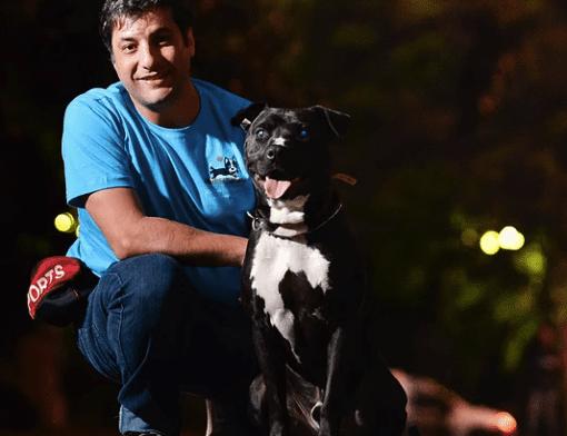 homem agachado ao lado de um cachorro