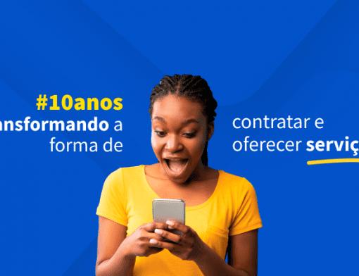 Imagem de uma mulher negra vestindo uma camiseta amarela e segurando um celular. O fundo da imagem é azul e tem a frase 10 anos transformando a forma de contratar e oferecer serviços